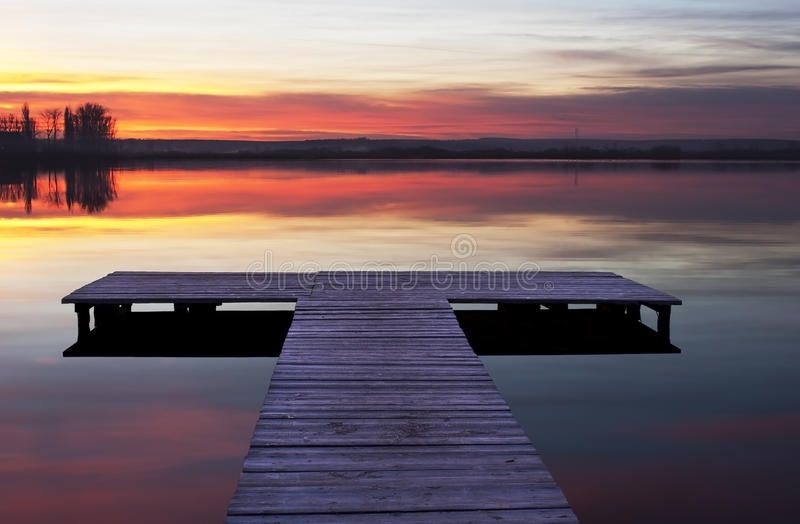 Jetty sunset. Photography of a lake and a jetty at the sunset stock image
