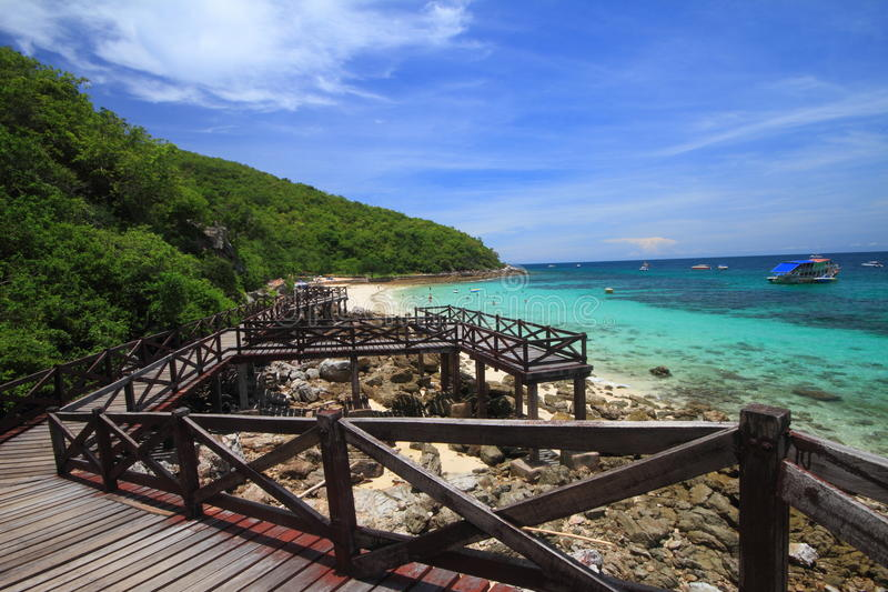 Jetty to a tropical beach on island stock images