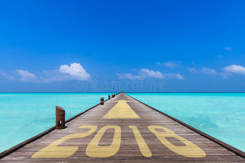 Jetty to 2018. Wooden jetty with the word 2018 and an yellow arrow showing forward to the horizon, business concept for turn of the year stock photography