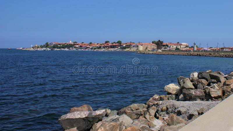 Jetty view of the penninsular town of Nessebar, Bulgaria. Bulgarian Black Sea town on a cloudless, sunny, summer day. The jetty cuts the colder blue water and royalty free stock photo