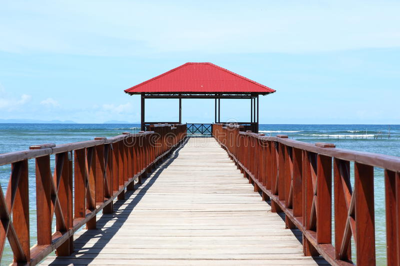 Jetty. Wooden jetty with penthouse with red roof on blue sea (Sorong, Papua Barat, Indonesia stock photo