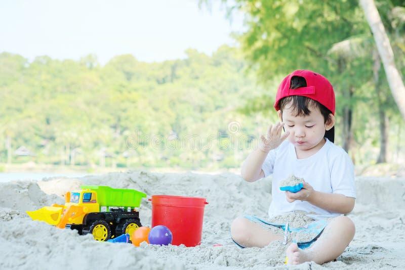 Jeu asiatique mignon d'enfant de plan rapproché avec le sable et le jouet sur le fond texturisé de plage photographie stock