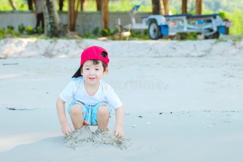 Jeu asiatique mignon d'enfant de plan rapproché avec le sable sur le fond texturisé de plage images stock