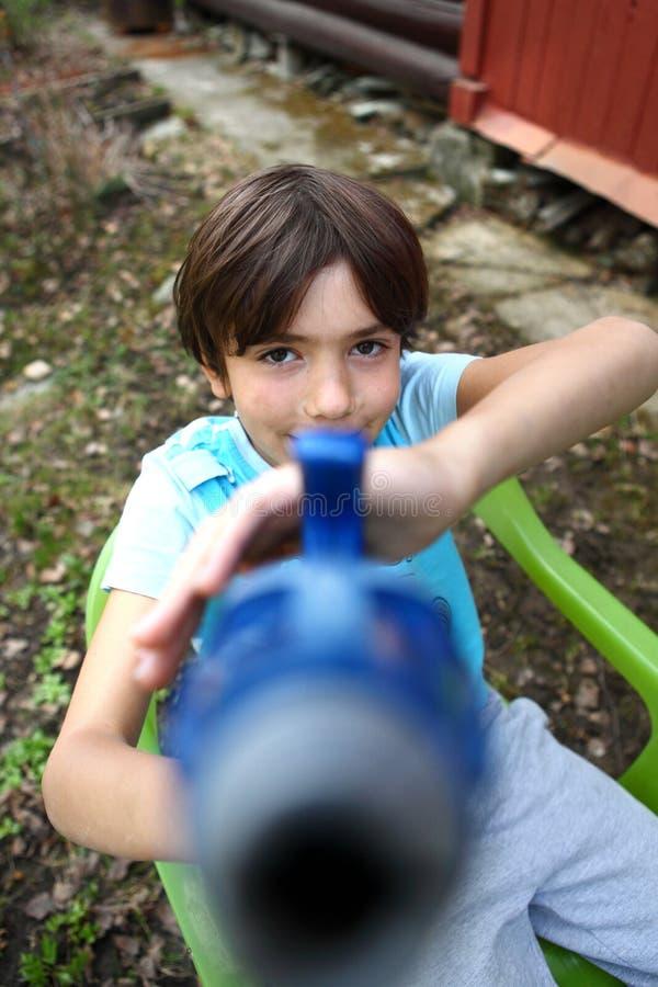 Jeu beau de la préadolescence de garçon avec l'arme à feu d'eau images libres de droits