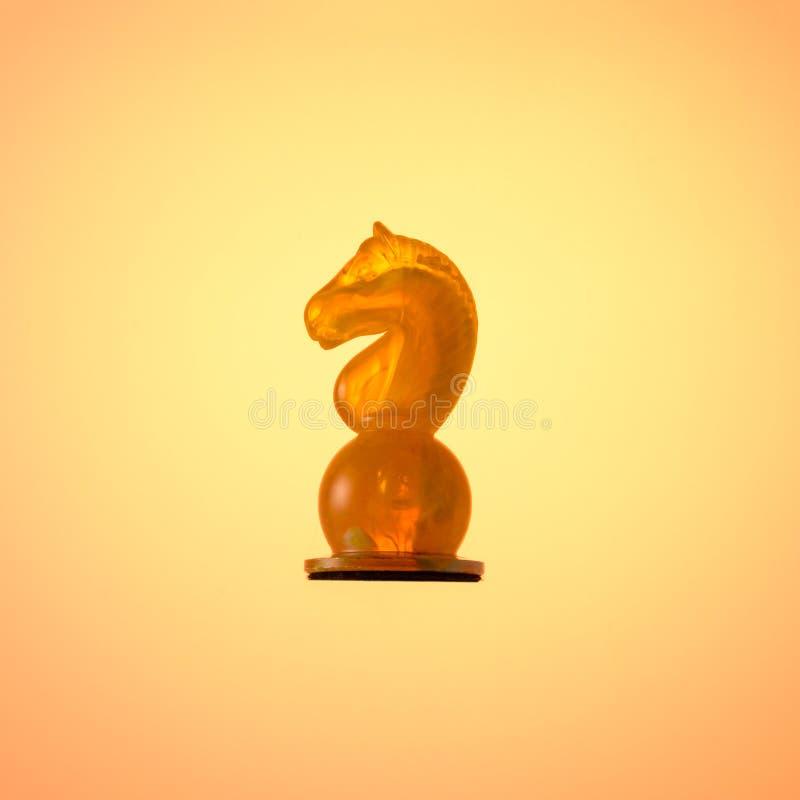 Jeu d'échecs ambre Chevalier blanc de pièce d'échecs sur le fond de gradient d'or images libres de droits