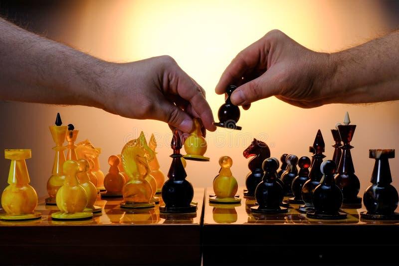 Jeu d'échecs avec les pièces d'échecs ambres sur le conseil Mains des joueurs tenant des gages Avec le fond d'or de gradient image stock