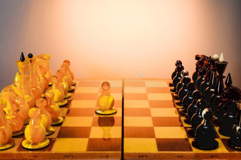 Jeu d'échecs avec les pièces d'échecs ambres sur le panneau sur la table blanche, premier mouvement E2-E4 Avec le fond d'or de photos stock