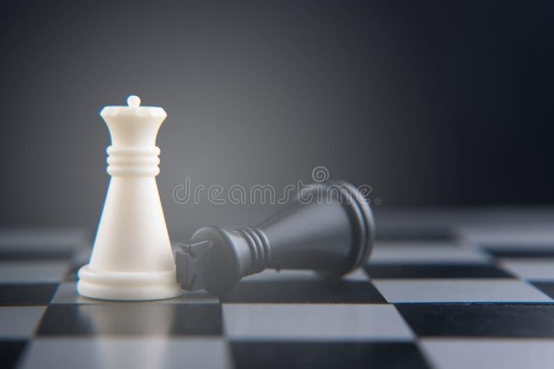 Jeu d'échecs sur l'échiquier roi noir tombé sur la reine blanche photos libres de droits