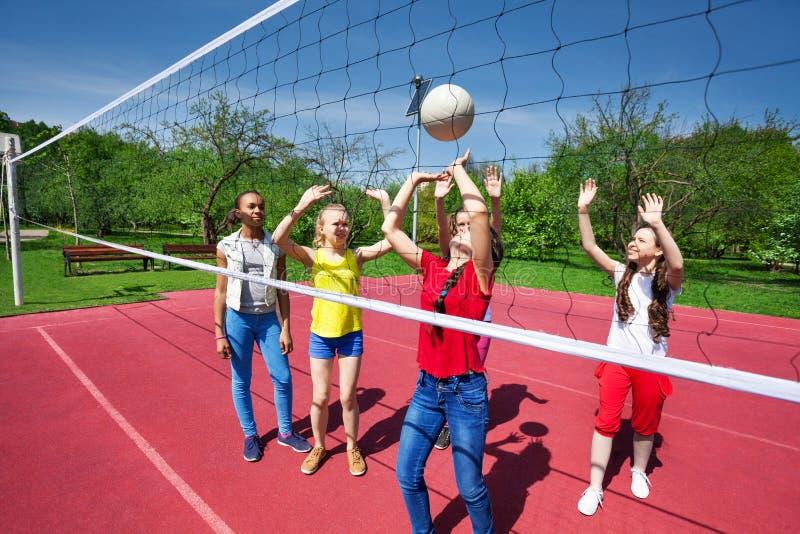 Jeu d'ados pendant le match de volley sur le terrain de jeu images libres de droits
