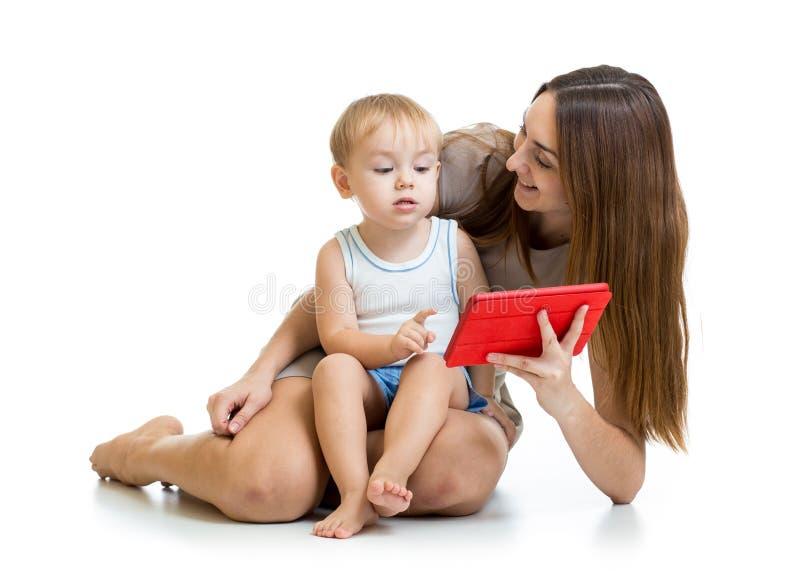 Jeu d'enfant de mère et de fils avec le PC de comprimé photo libre de droits