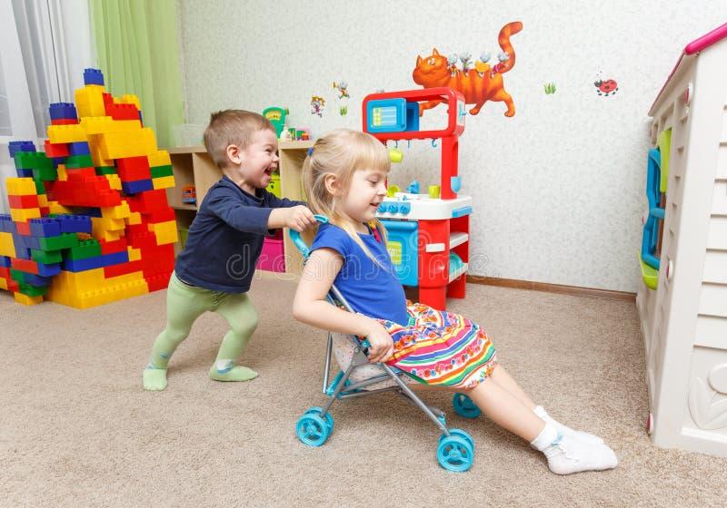 Jeu d'enfants avec la poussette de jouet dans la garde images stock