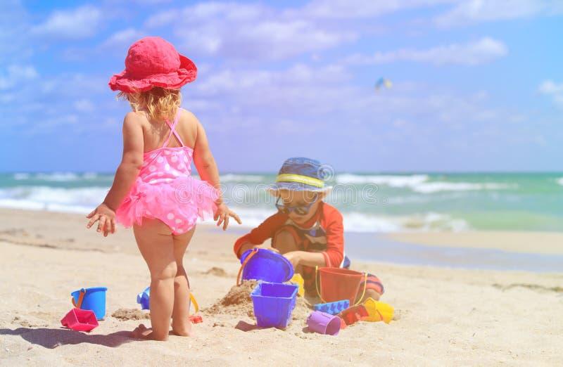 Jeu d'enfants avec le sable sur la plage d'été photo libre de droits