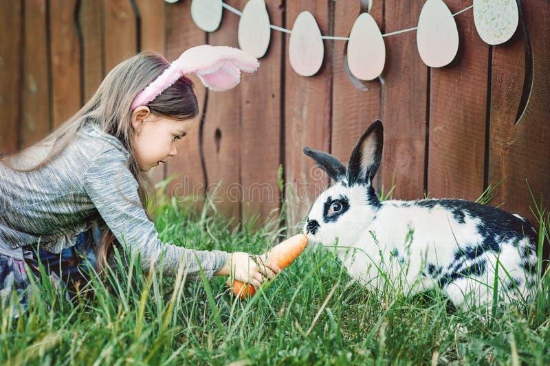 Jeu d'enfants avec le vrai lapin L'enfant riant à l'oeuf de pâques chassent avec le lapin blanc d'animal familier Petite fille d' image libre de droits