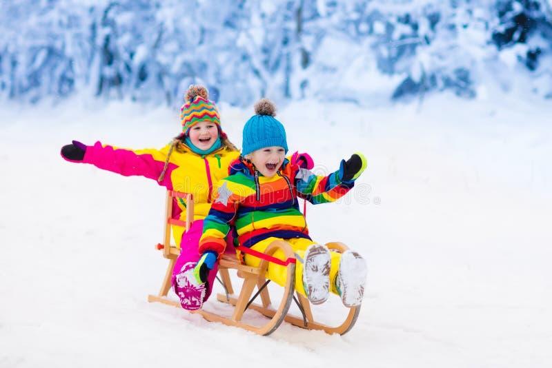 Jeu d'enfants dans la neige Tour de traîneau d'hiver pour des enfants images stock