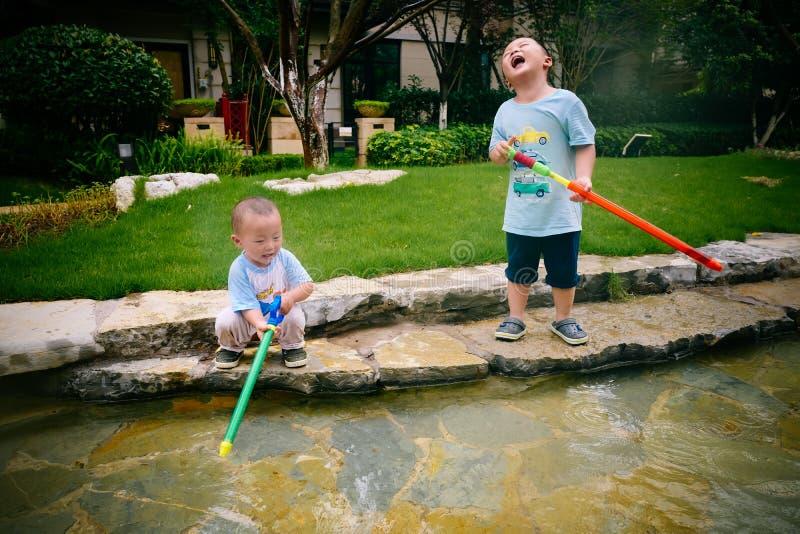 Jeu d'enfants dans le jardin avec des armes à feu et des fusils de l'eau photo libre de droits