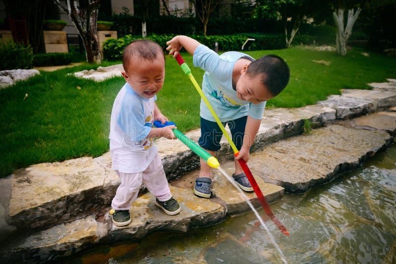 Jeu d'enfants dans le jardin avec des armes à feu et des fusils de l'eau photographie stock libre de droits