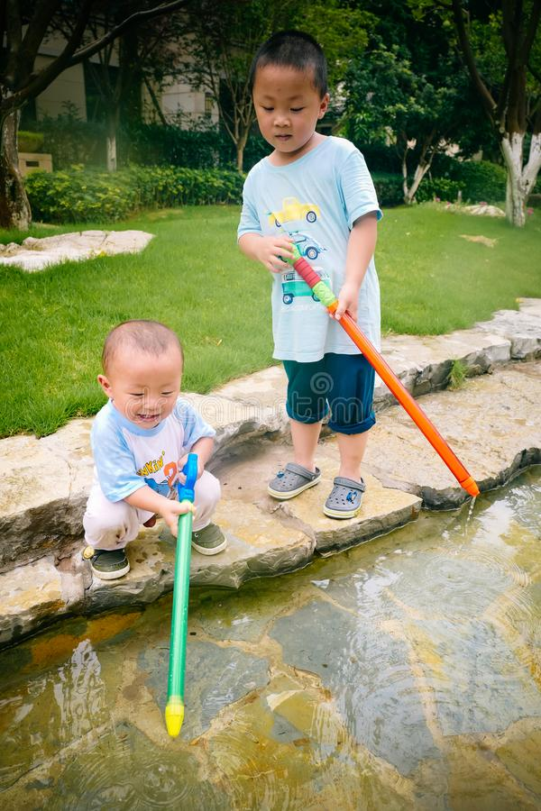 Jeu d'enfants dans le jardin avec des armes à feu et des fusils de l'eau photographie stock