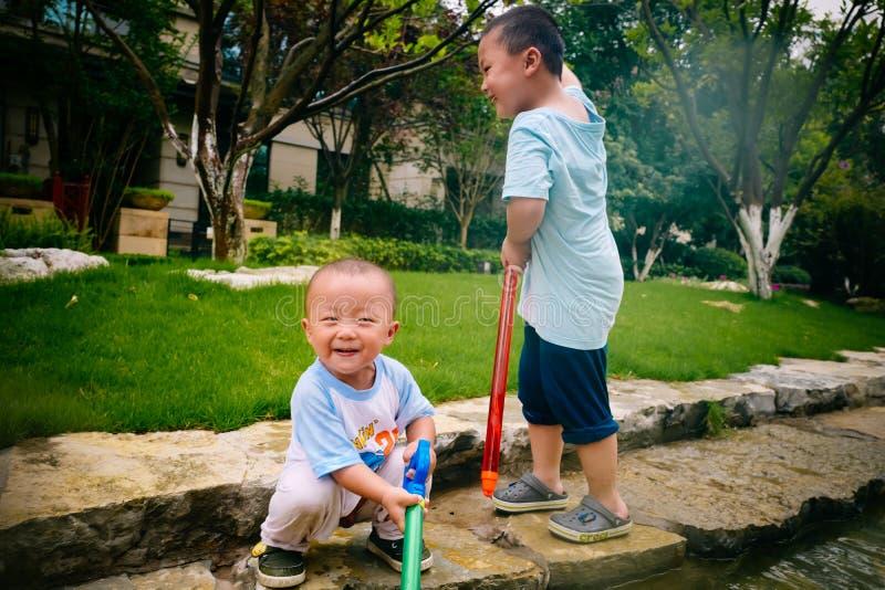 Jeu d'enfants dans le jardin avec des armes à feu et des fusils de l'eau images libres de droits