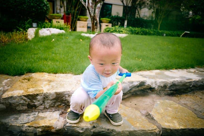 Jeu d'enfants dans le jardin avec des armes à feu et des fusils de l'eau image libre de droits