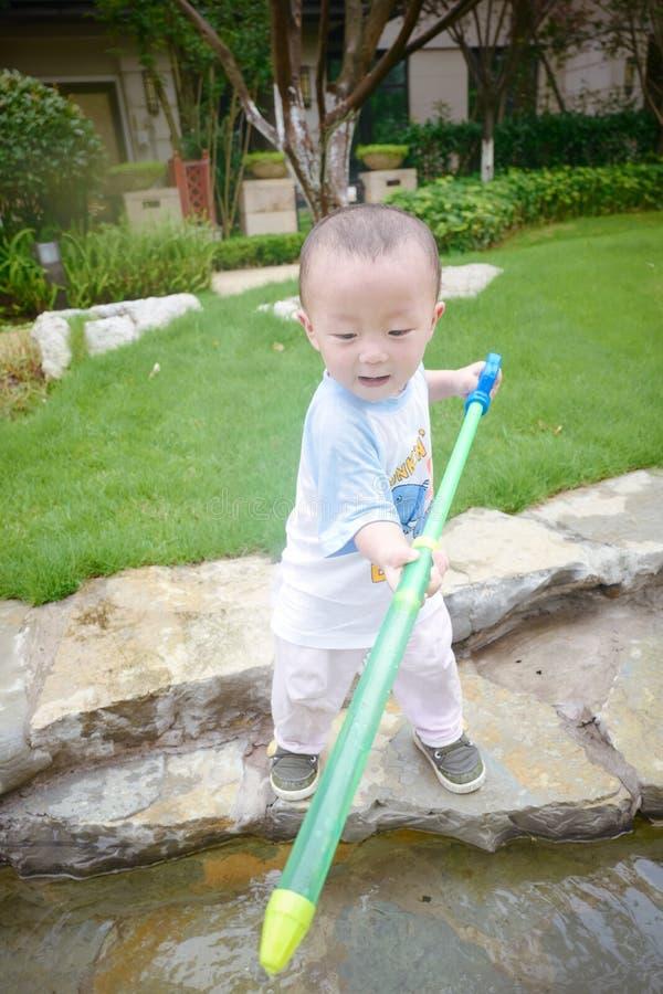 Jeu d'enfants dans le jardin avec des waterguns photos libres de droits