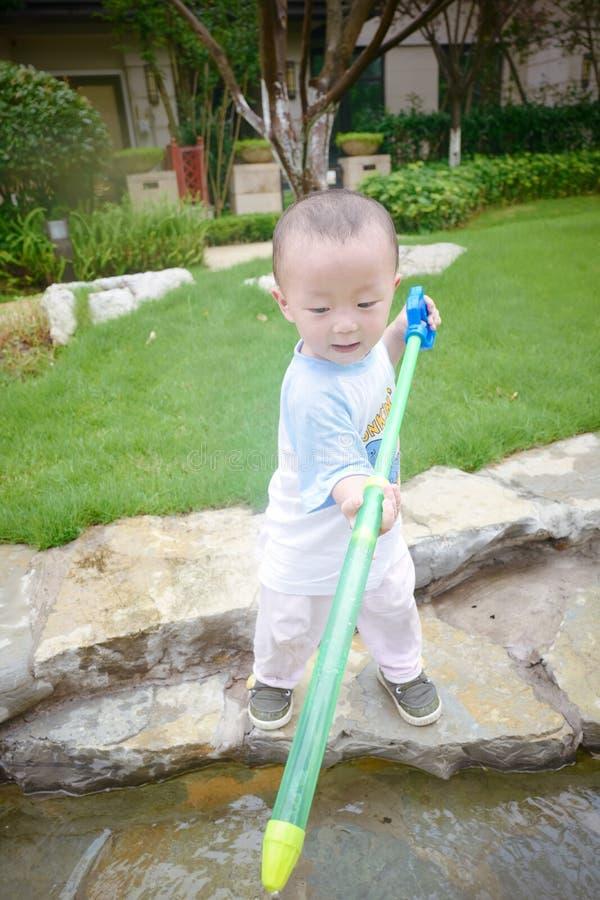 Jeu d'enfants dans le jardin avec des waterguns image libre de droits
