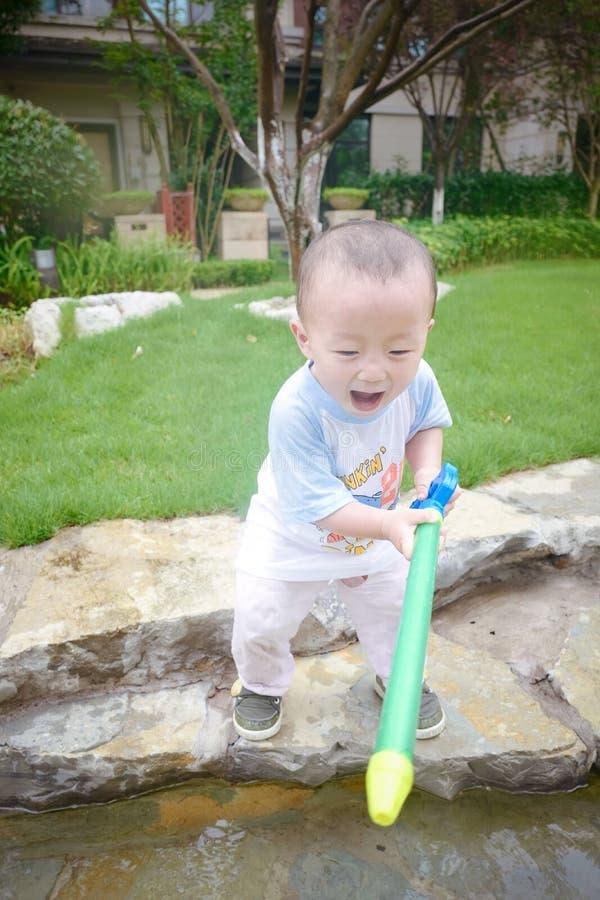 Jeu d'enfants dans le jardin avec des waterguns photographie stock libre de droits