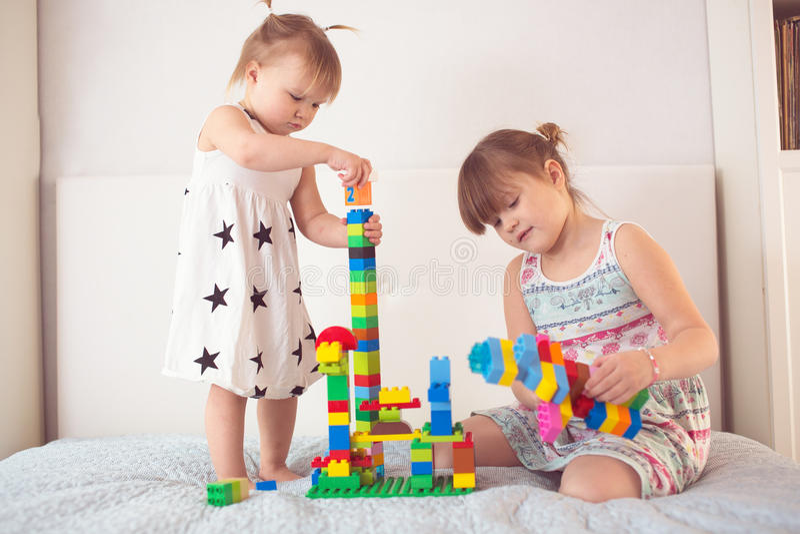 Jeu d'enfants de mêmes parents avec le constructeur dans le vrai intérieur photographie stock libre de droits