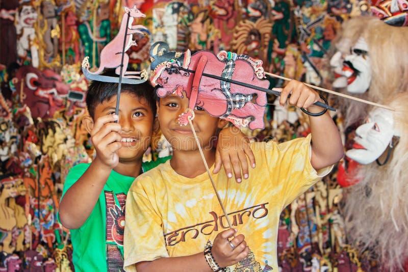 Jeu d'enfants de Smiley Balinese avec des marionnettes d'ombre images libres de droits