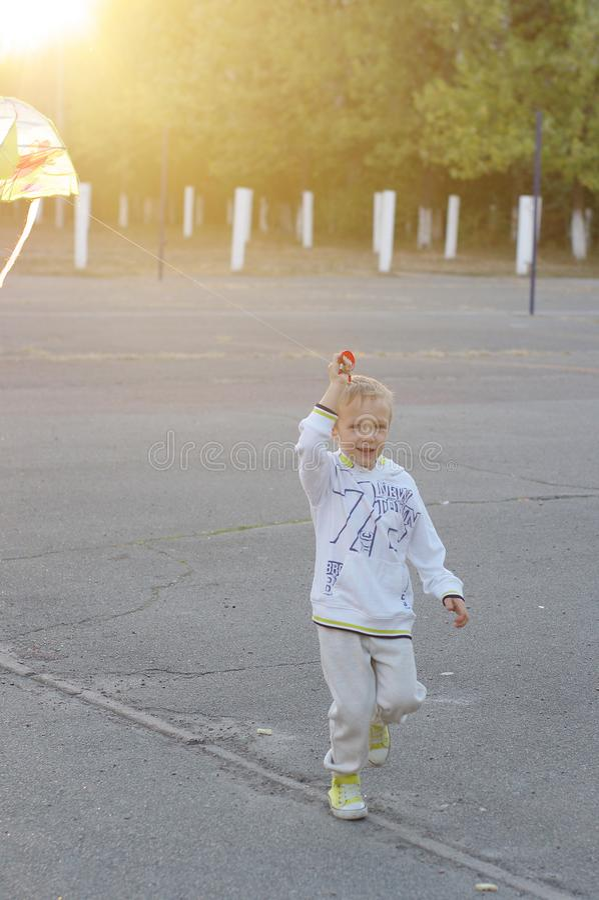 Jeu d'enfants drôle et heureux dans un cerf-volant Ils sont habillés dans les pulls molletonnés et le pantalon blancs Fonctionnem photos stock