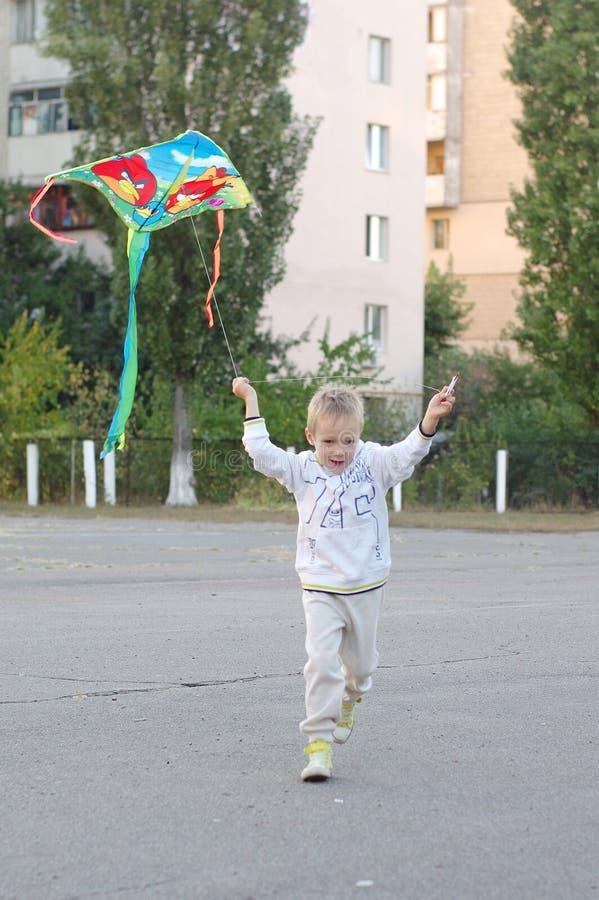 Jeu d'enfants drôle et heureux dans un cerf-volant Ils sont habillés dans les pulls molletonnés et le pantalon blancs Fonctionnem photo stock