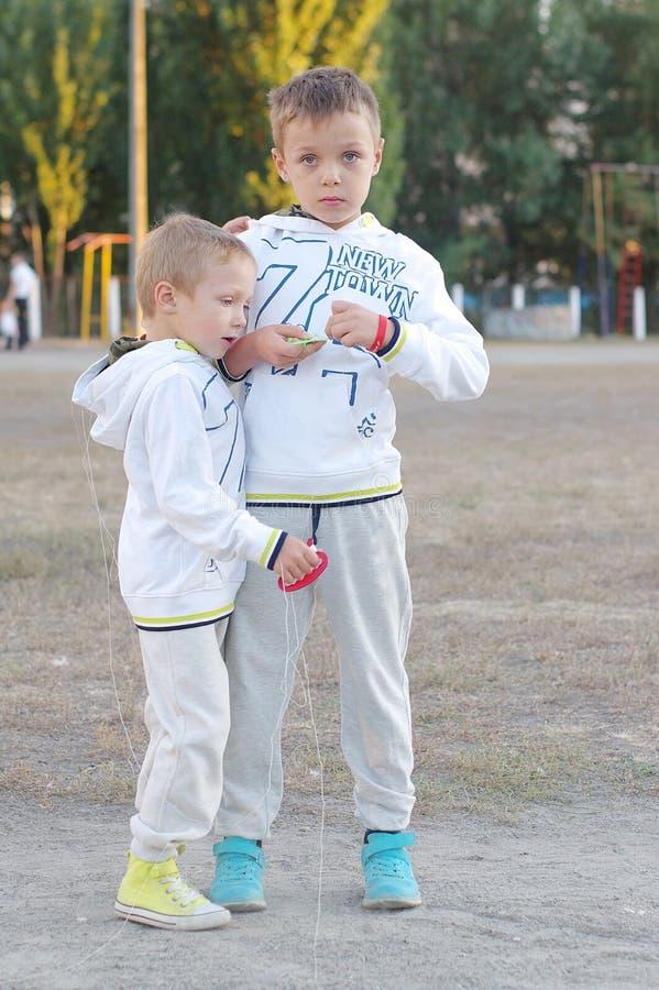 Jeu d'enfants drôle et heureux dans un cerf-volant Ils sont habillés dans les pulls molletonnés et le pantalon blancs Fonctionnem image stock