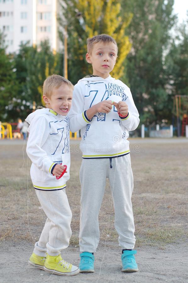 Jeu d'enfants drôle et heureux dans un cerf-volant Ils sont habillés dans les pulls molletonnés et le pantalon blancs Fonctionnem photographie stock libre de droits