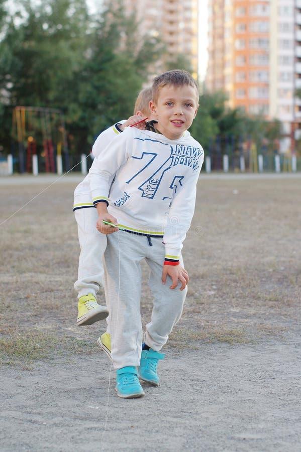 Jeu d'enfants drôle et heureux dans un cerf-volant Ils sont habillés dans les pulls molletonnés et le pantalon blancs Fonctionnem photos libres de droits