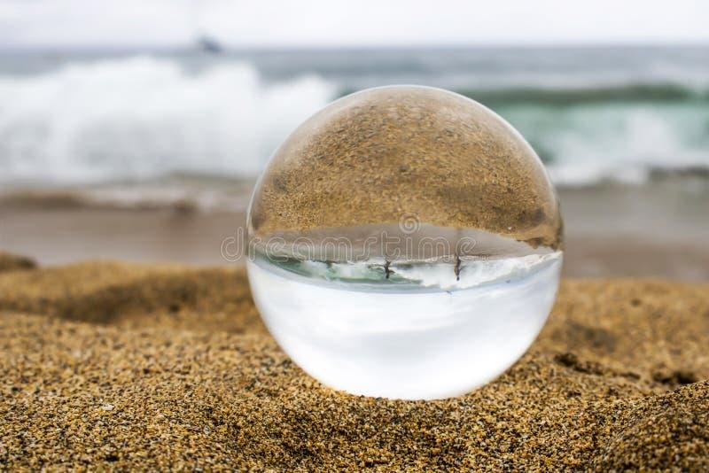 Jeu d'enfants en grand ressac à la plage dans la boule en verre images stock