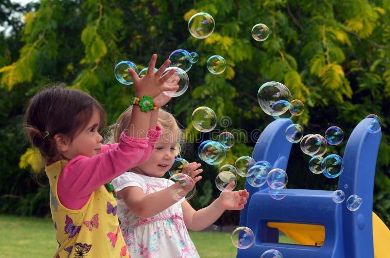 Jeu d'enfants heureux avec des bulles de savon photo stock