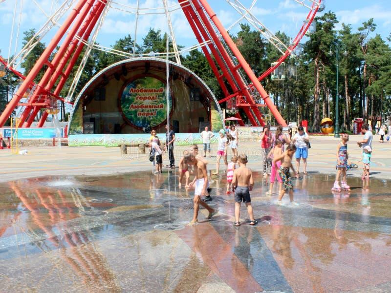 Jeu d'enfants sur le terrain de jeu avec des fontaines en été chaud image libre de droits
