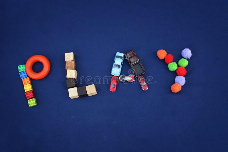 JEU d'inscription fait à partir de différents jouets sur le backgr bleu de textile photos stock