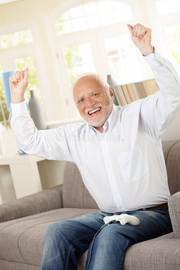 Jeu d'ordinateur de gain heureux aîné photo stock