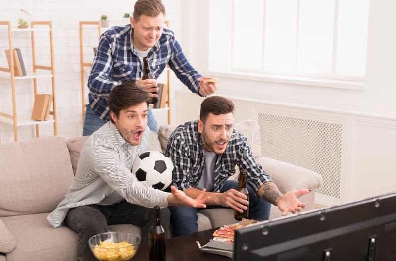 jeu d?truit Passionés du football fâchés regardant la rencontre à la maison photographie stock
