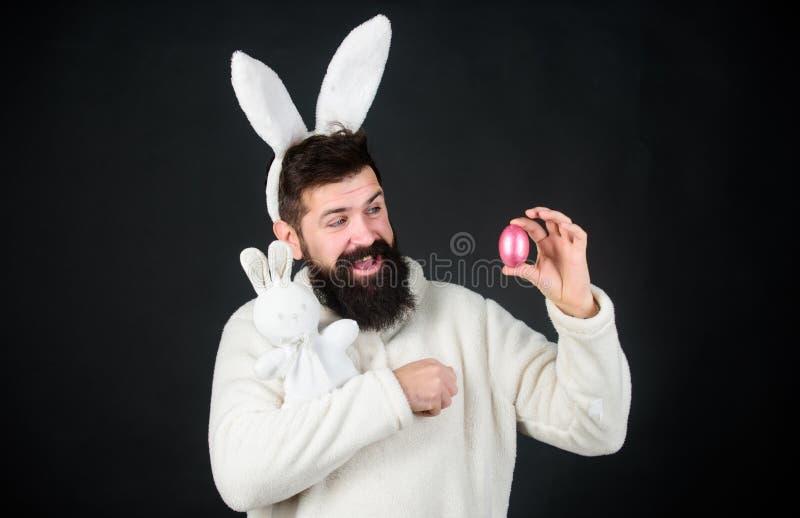 Jeu de chasse à oeufs Lapin doux mignon de hippie barbu de type avec le fond noir de longues oreilles blanches Vieille femme d'Af images stock