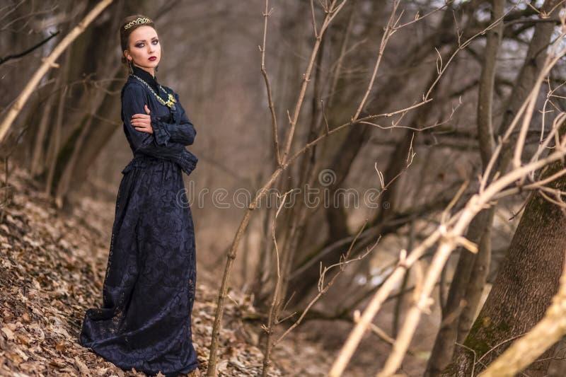 Jeu de costume Jeune femelle caucasienne de brune en Art Dress avec le collier et la couronne posant en Forest Outdoors images stock