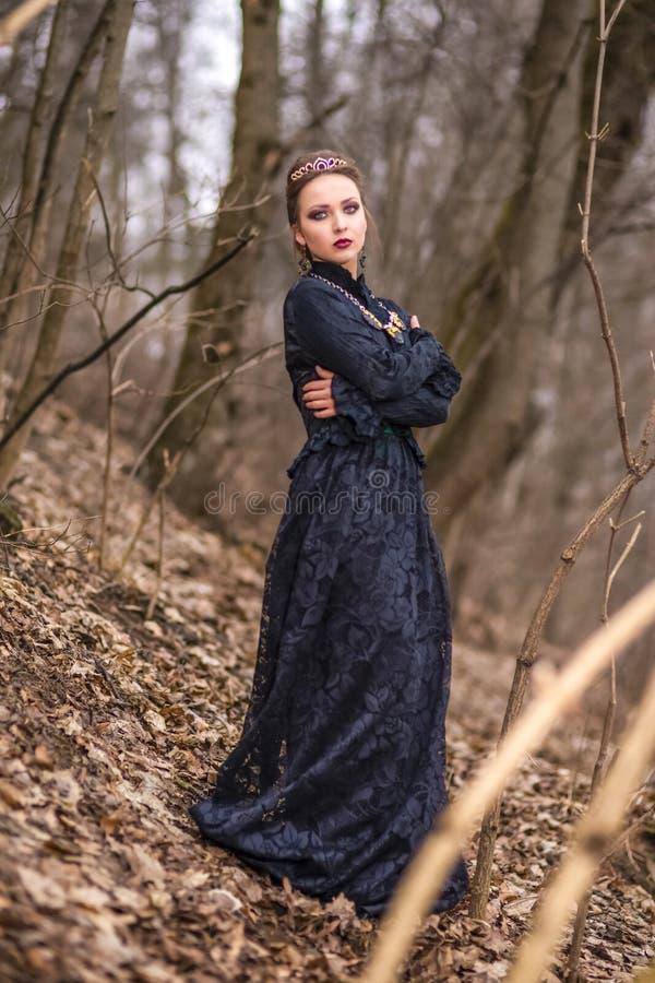 Jeu de costume Jeune femelle caucasienne de brune en Art Dress avec le collier et la couronne posant en Forest Outdoors photographie stock libre de droits