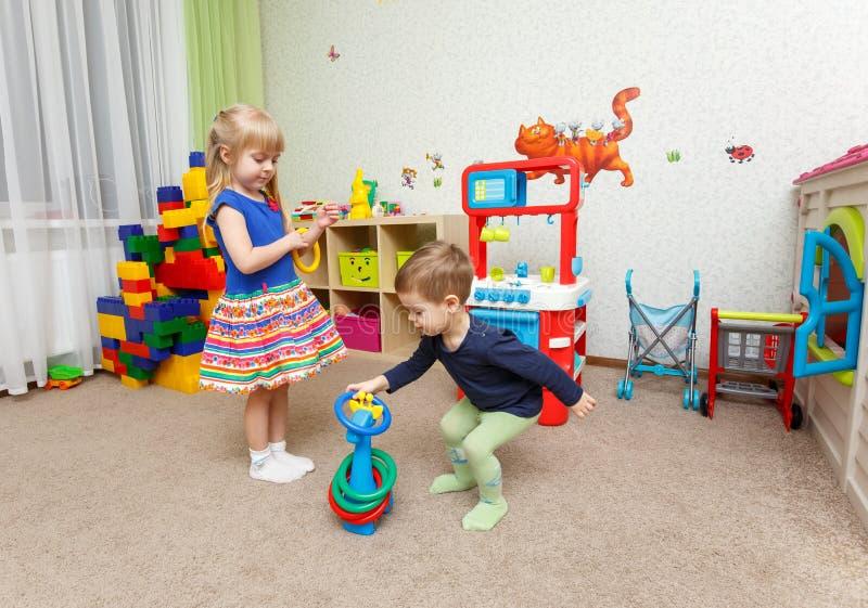 Jeu de deux enfants avec les anneaux en plastique dans le jardin d'enfants images libres de droits