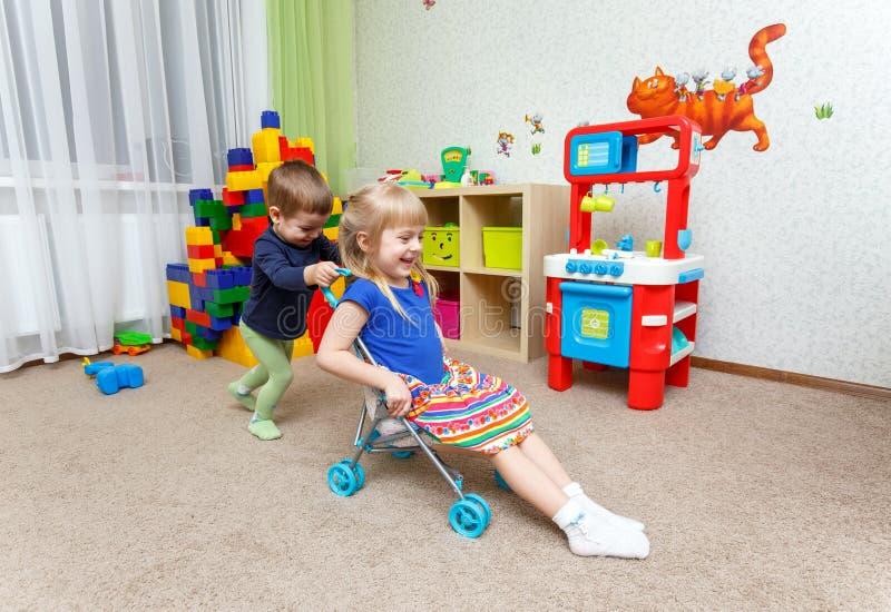 Jeu de deux enfants heureux avec la poussette de jouet dans la garde image libre de droits