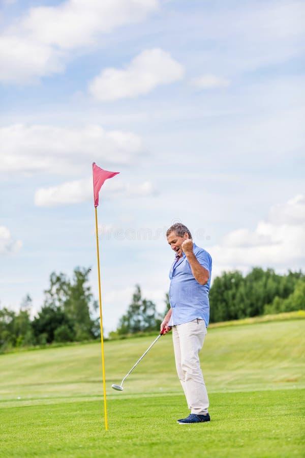 Jeu de gain d'homme supérieur sur un terrain de golf images stock