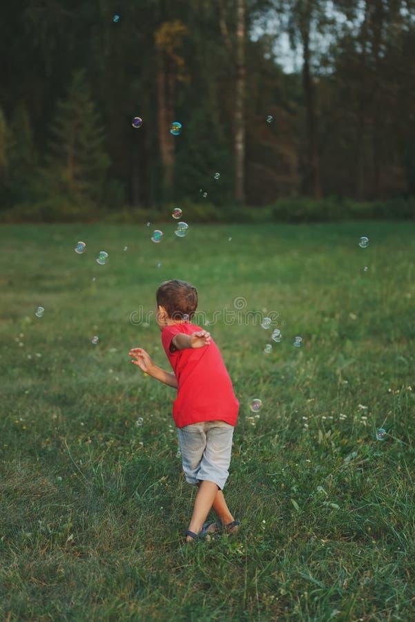 Jeu de garçon avec des bulles de savon en parc photos stock