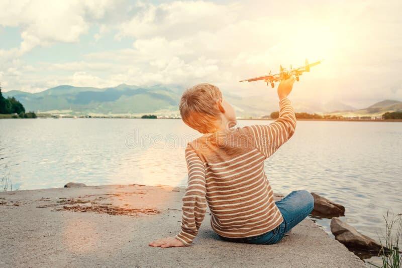 Jeu de garçon avec la séance plate de jouet près du lac image stock
