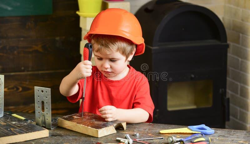 Jeu de garçon comme constructeur ou réparateur, travail avec des outils Badinez le garçon dans le casque antichoc ou le casque or photos libres de droits