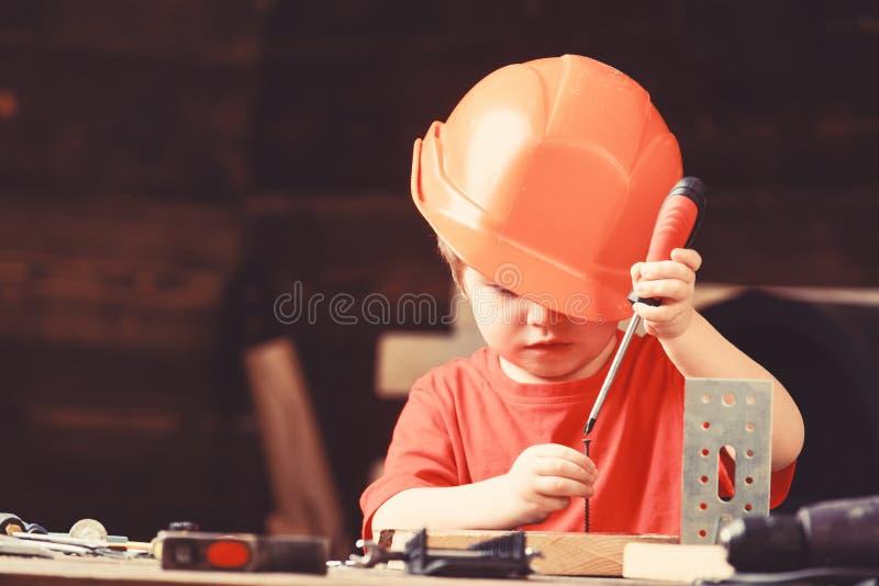 Jeu de garçon comme constructeur ou réparateur, travail avec des outils Enfant rêvant de la future carrière dans l'architecture o images stock