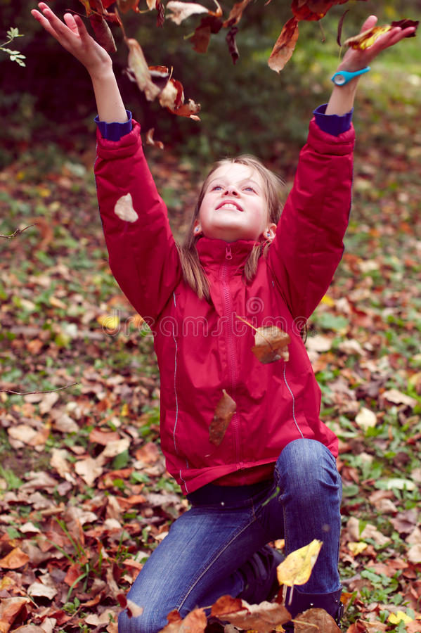 Jeu de l'adolescence de fille avec des lames d'automne vers le haut dans le ciel photographie stock